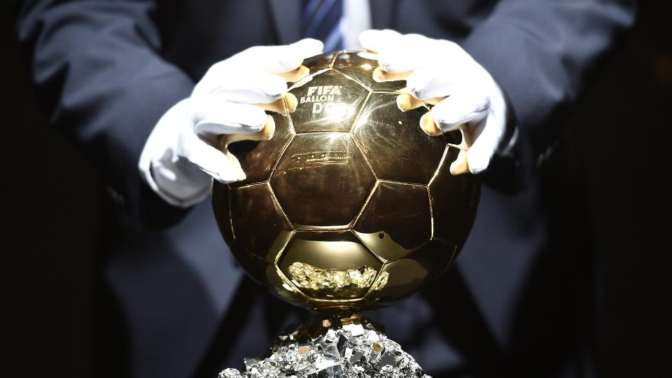 A steward touches the 2014 FIFA Ballon d'Or award ahead of the award ceremony at the Kongresshaus in Zurich on January 12, 2015.  AFP PHOTO / FABRICE COFFRINI        (Photo credit should read FABRICE COFFRINI/AFP/Getty Images)